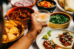 Mexican Food Spread hand holding glass of horchata 16x9 b8f3a04a 5371 4a44 a78c 59d6d50d64e7 image
