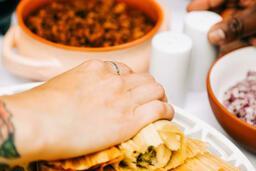 Mexican Food Spread hand grabbing a tamale 16x9 64b8ff52 b326 4d9e 931d 9f8d5a822071 image