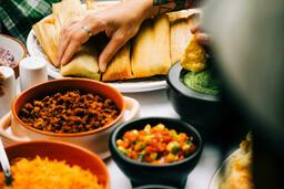 Mexican Food Spread hand grabbing a tamale 16x9 d4e7265a 3844 412b 9159 909178868a6e image