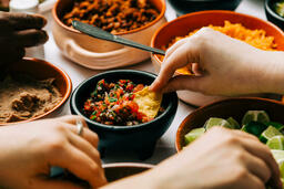 Mexican Food Spread hand dipping chip in salsa 16x9 6f328e89 92ae 4284 a387 de293d901208 image