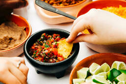 Mexican Food Spread hand dipping chip in salsa 16x9 5001789b dc17 4e3c 876c 8b361b14cb5c image