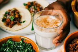Mexican Food Spread hand holding cup of horchata 16x9 01fd5da9 3dd1 4b8c 8c6c 0635edf248df image
