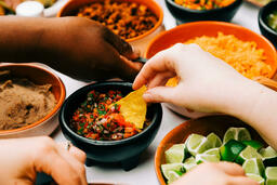 Mexican Food Spread hand dipping chip in salsa 16x9 682cbef1 157b 4b90 9774 2c16a279d4e1 image