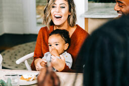 Woman Laughing at Thanksgiving Table, Holding Baby  image 2