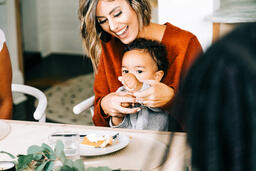 Woman Laughing at Thanksgiving Table, Holding Baby  image 1