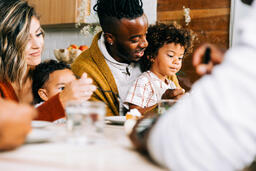 Family Seated Together at the Table Enjoying Thanksgiving Dessert  image 4