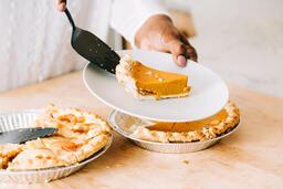 Woman Serving Up Slice of Pumpkin Pie  image 1