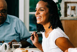 Woman Laughing with Family and Enjoying Thanksgiving Dinner  image 2