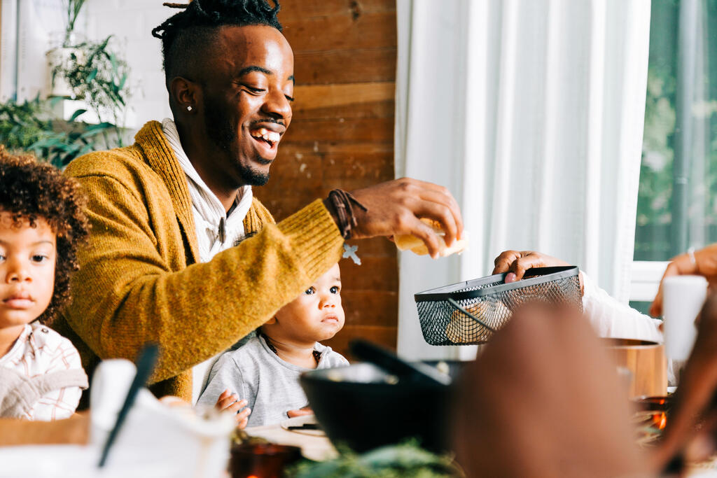 Man Grabbing a Dinner Roll From the Bread Basket at Thanksgiving Dinner large preview