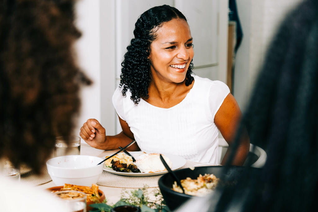Woman Laughing and Enjoying Thanksgiving Dinner large preview