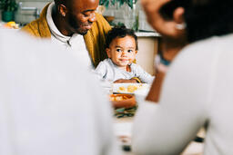 Father Holding Baby at the Thanksgiving Table  image 1