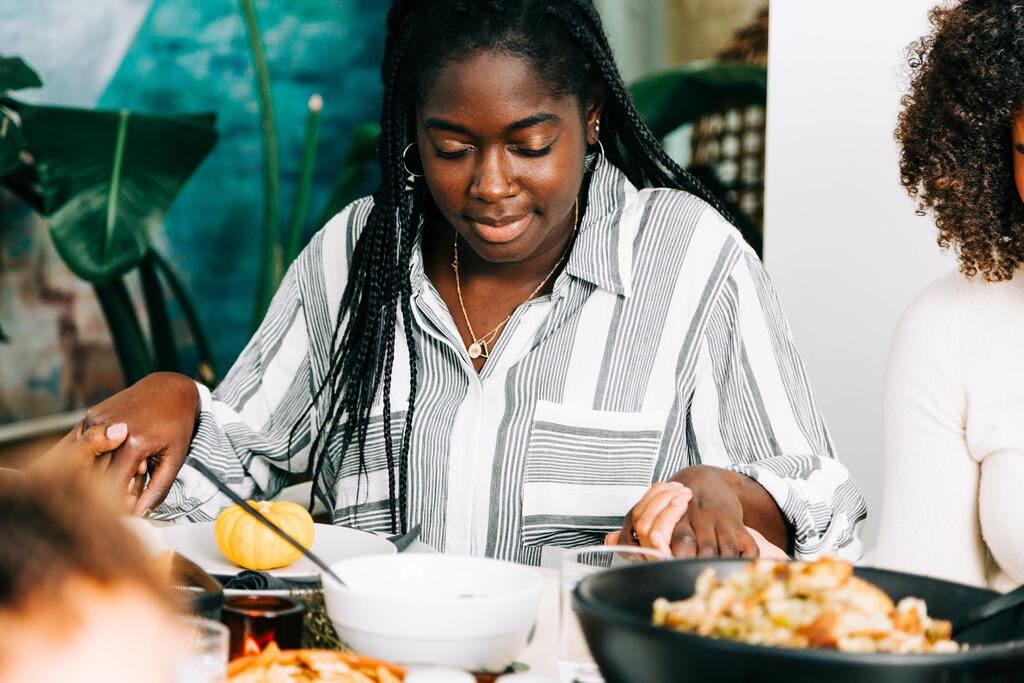 Woman with Head Bowed in Prayer Before the Thanksgiving Meal large preview