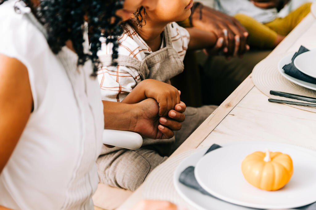 Woman and Child Holding Hand in Prayer Before the Thanksgiving Meal large preview
