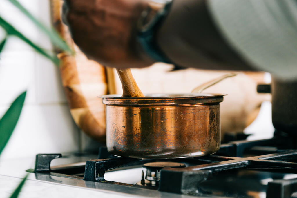 Man Stirring Apple Cider on Stovetop large preview