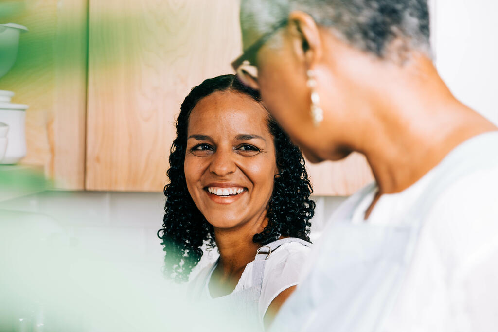 Mother and Daughter Laughing Together in the Kitchen large preview