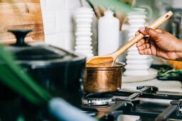 Woman Stirring Apple Cider on Stovetop  image 2