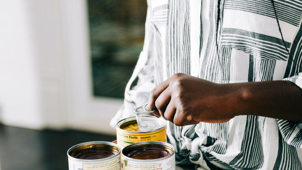Woman Opening Up Canned Food Items large preview