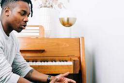 Man Sitting Next to Piano  image 2