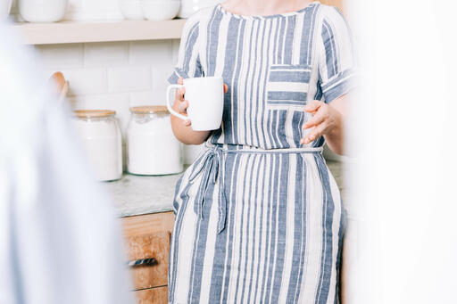 Woman Holding Cup of Coffee and having Conversation in the Kitchen