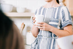 Woman Holding Cup of Coffee and having Conversation in the Kitchen  image 1