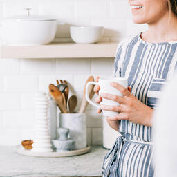 Woman Holding Cup of Coffee and having Conversation in the Kitchen  image 3