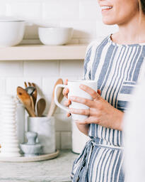 Woman Holding Cup of Coffee and having Conversation in the Kitchen  image 4