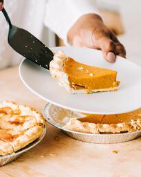 Woman Serving Up Slice of Pumpkin Pie  image 3