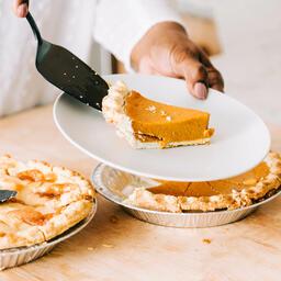 Woman Serving Up Slice of Pumpkin Pie  image 2