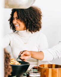 Woman Laughing as Family Serves Up Thanksgiving Dinner  image 2