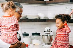 Woman Baking Christmas Cookies with her Grandchildren  image 1