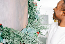 Man Decorating for Christmas with Garland  image 1