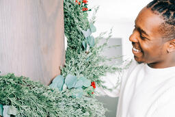 Man Decorating for Christmas with Garland  image 2