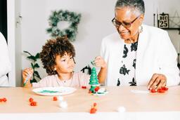 Grandmother and Grandson Doing a Christmas Craft Together  image 1