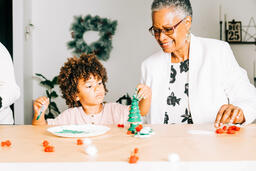 Grandmother and Grandson Doing a Christmas Craft Together  image 3