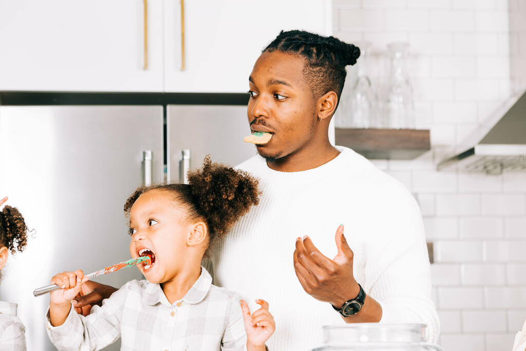Father and Daughter Frosting and Eating Christmas Cookies Together large preview