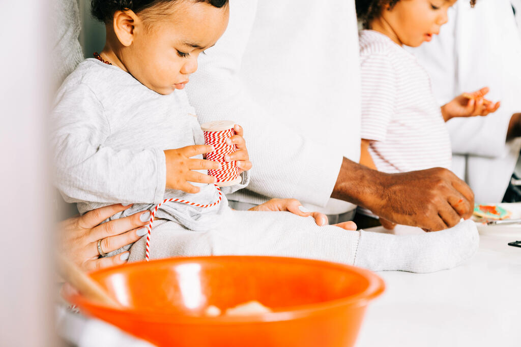 Baby Playing with Red String While Family Bakes in the Kitchen large preview
