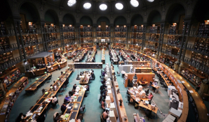 An image of a large library with many people studying, seen from the view of a high-up balcony