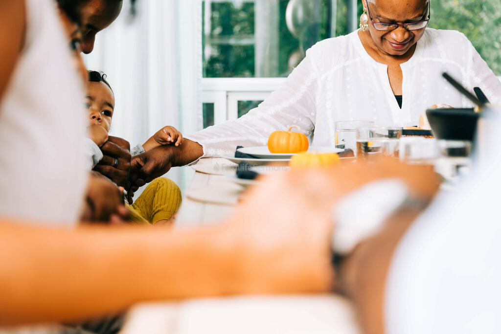 Family Praying Together Before the Thanksgiving Meal large preview