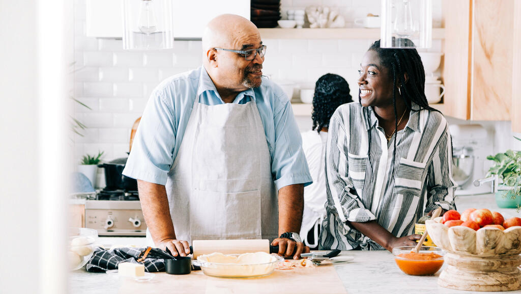 Father and Daughter Laughing Together While Preparing the Thanksgiving Meal large preview