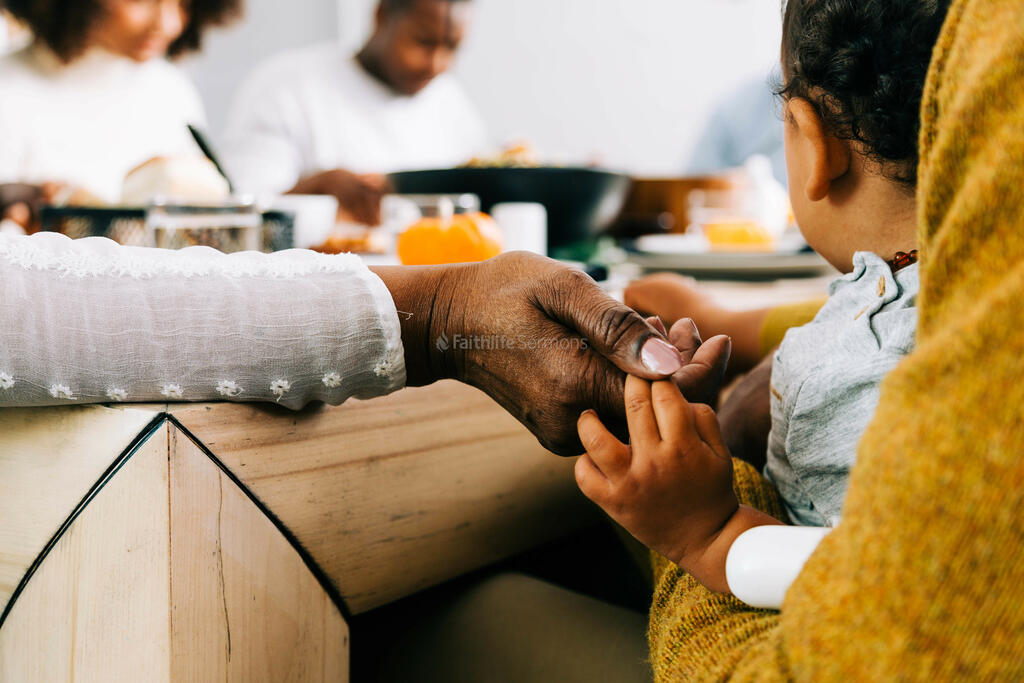 Grandmother and Baby Holding Hands in Prayer Before the Thanksgiving Meal large preview