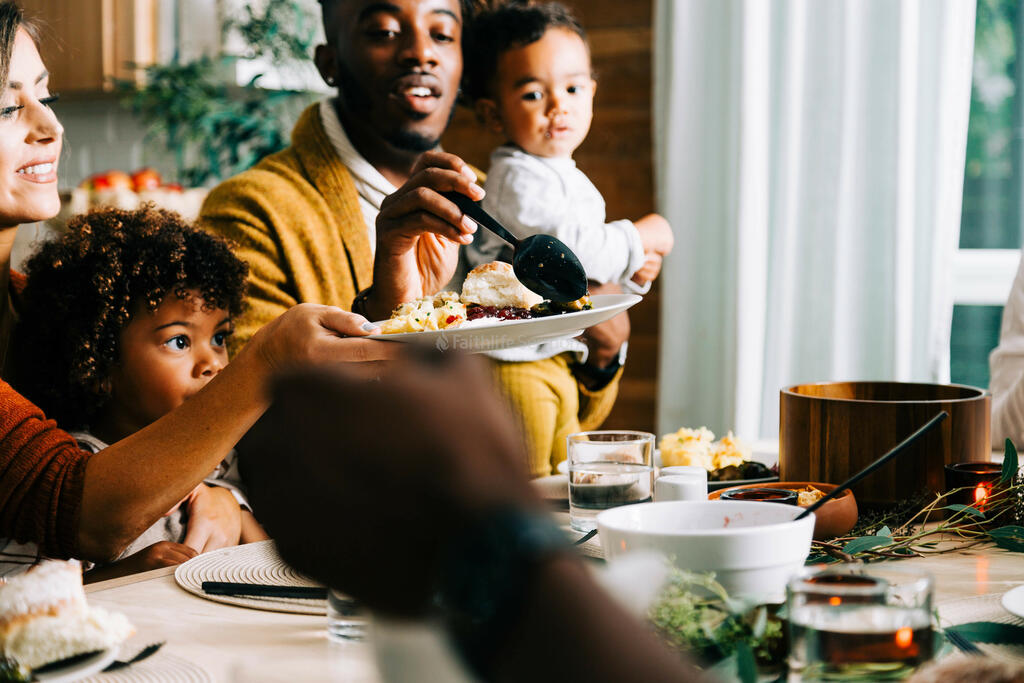 Man Serving Food onto Woman's Plate at the Thanksgiving Table large preview