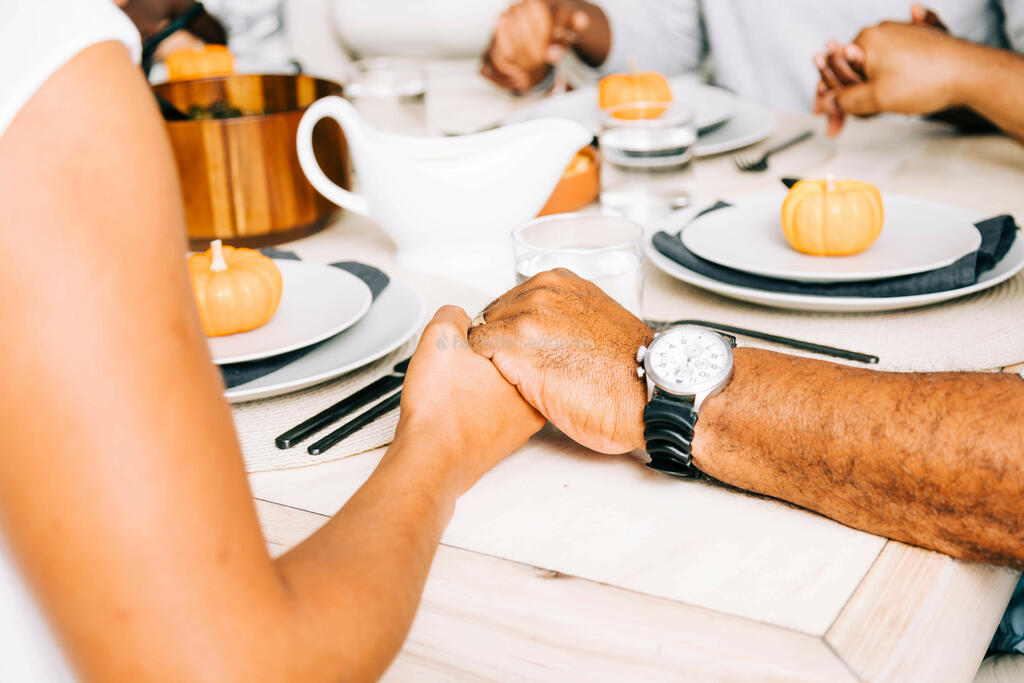 Holding Hands in Prayer at Thanksgiving Table large preview