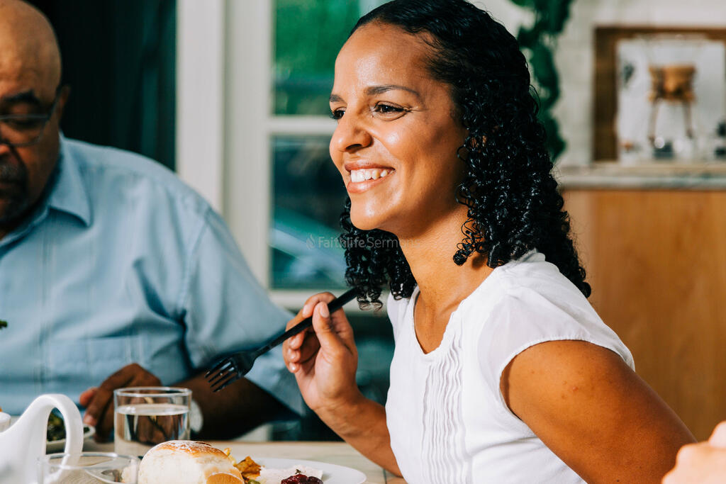 Woman Laughing with Family and Enjoying Thanksgiving Dinner large preview