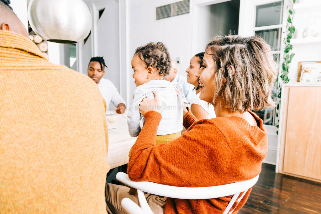 Woman Holding Baby and Laughing at the Thanksgiving Table large preview