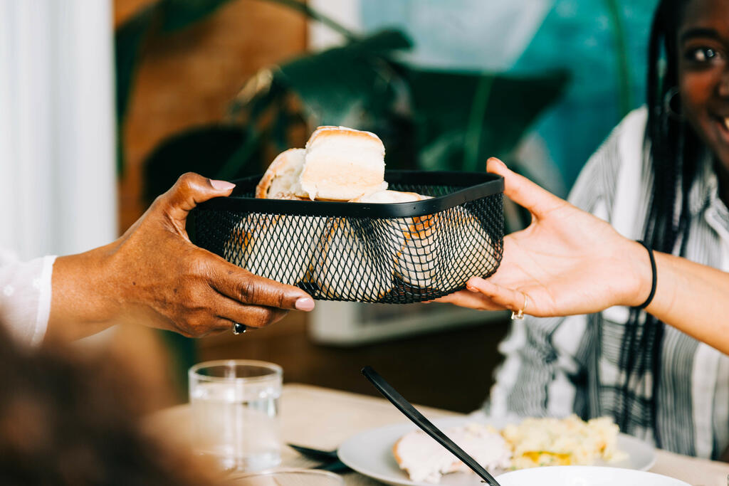 Hands Passing the Bread Basket at the Thanksgiving Table large preview