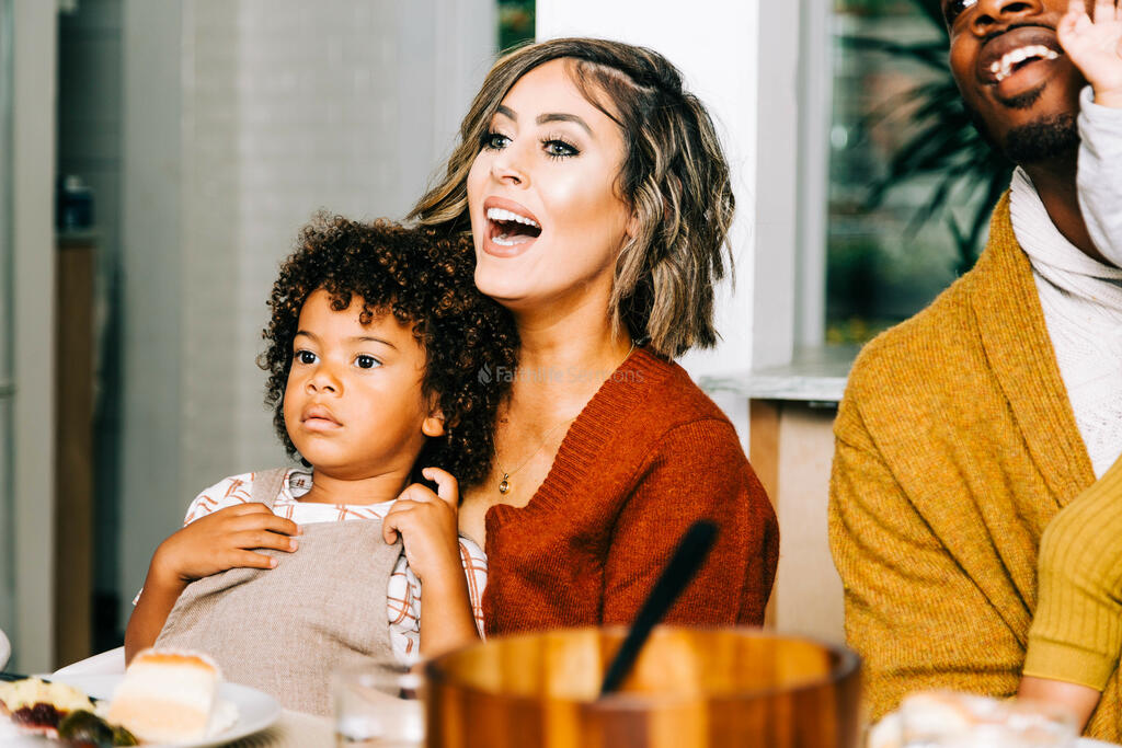 Mother Holding Son in Lap While Laughing with Family at the Thanksgiving Table large preview