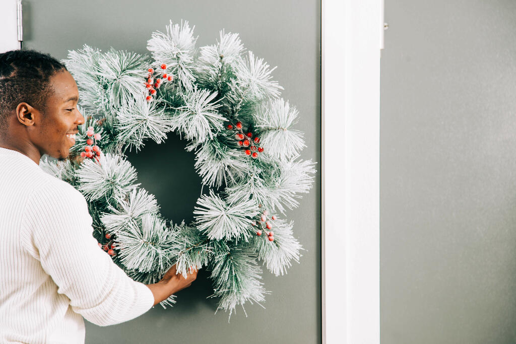 Man Putting a Wreath on the Door for Christmas large preview