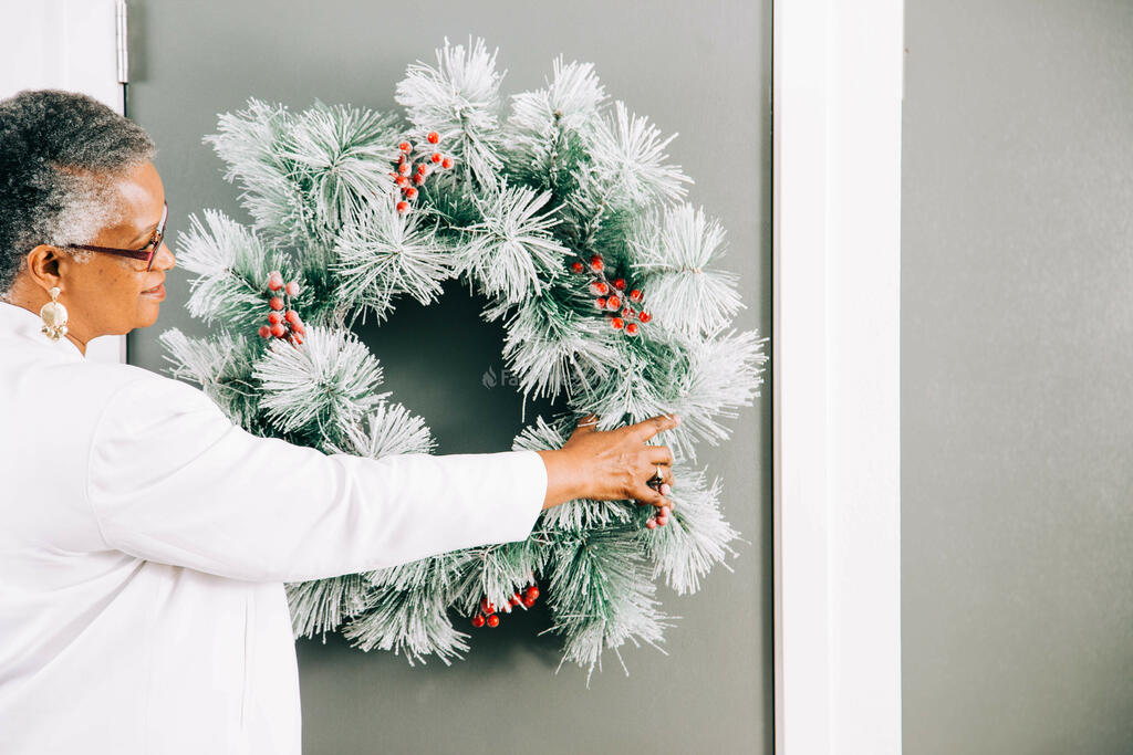 Woman Putting a Wreath on the Door for Christmas large preview