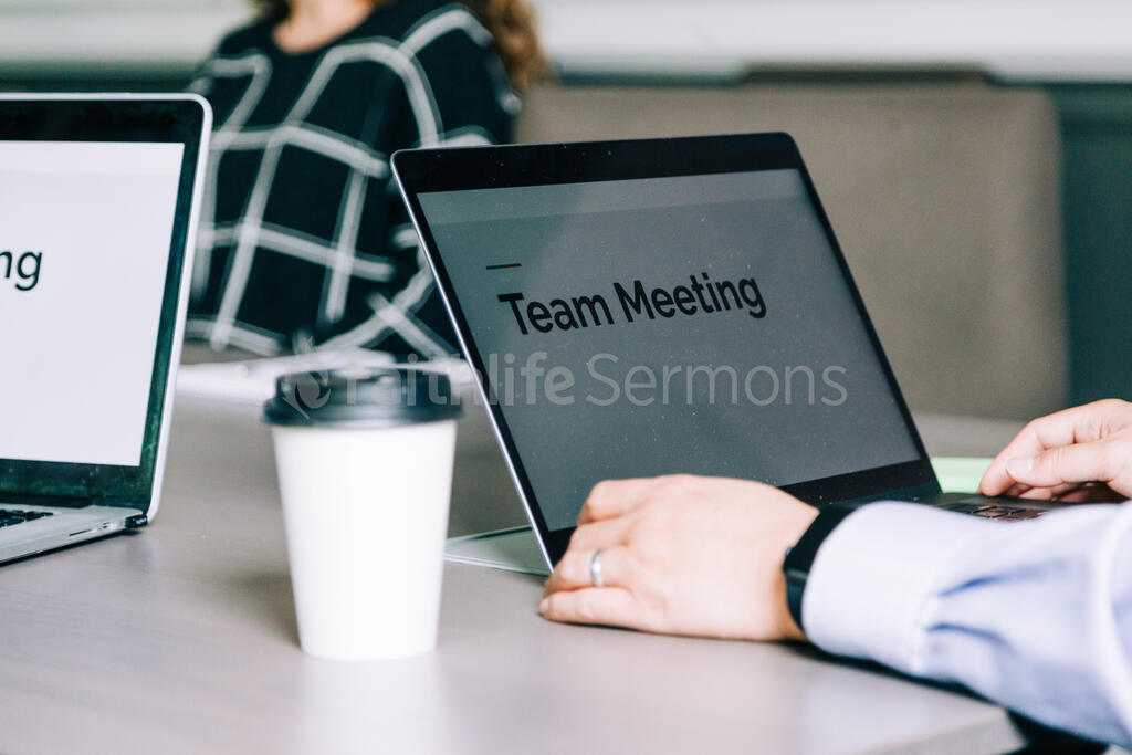 Man at Conference Table with Laptop Open During a Meeting large preview