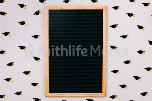 Letterboard Surrounded by Graduation Caps